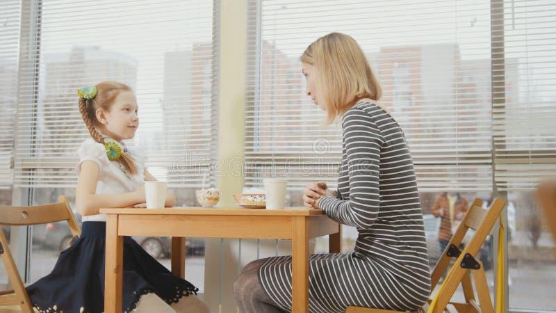Η νέες μητέρα και η κόρη τρώνε caks και πίνουν στο αρτοποιείο στοκ εικόνες