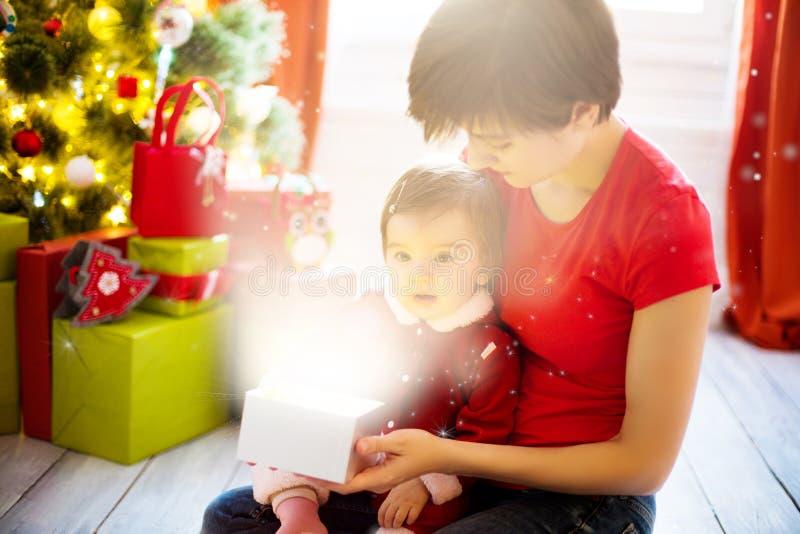 Η νέες μητέρα και λίγη κόρη έντυσαν ως Άγιος Βασίλης που ανοίγει ένα μαγικό δώρο Χριστουγέννων από ένα χριστουγεννιάτικο δέντρο στοκ φωτογραφία