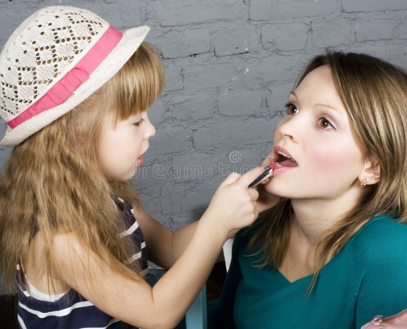 Η νέες οικογενειακές μητέρα και η κόρη αποτελούν στον καθρέφτη στοκ εικόνες με δικαίωμα ελεύθερης χρήσης