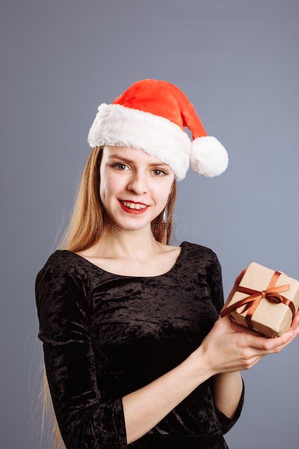 Η νεαρή Καυκάσα με κόκκινο χριστουγεννιάτικο καπέλο και μαύρο φόρεμα, μου δίνει ένα κουτί με δώρα σε γκρι φόντο στοκ φωτογραφία με δικαίωμα ελεύθερης χρήσης