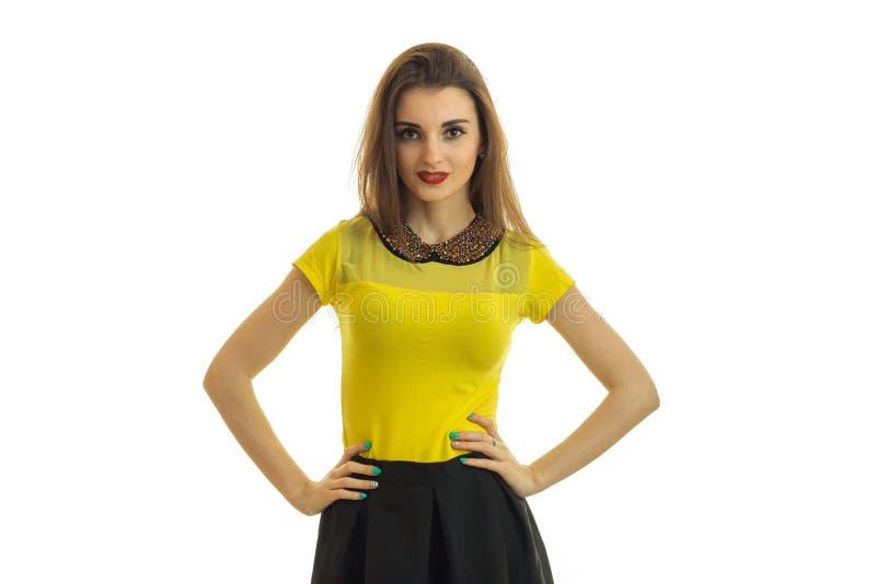 Η νεολαία ένα θαυμάσιο κορίτσι σε ένα φωτεινό σακάκι εξετάζει τη κάμερα και κρατά τα χέρια της στις πλευρές στοκ εικόνες με δικαίωμα ελεύθερης χρήσης