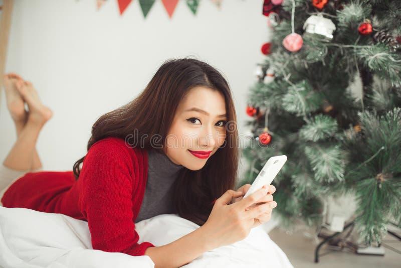 Η νεολαία που χαμογελά την ασιατική γυναίκα χρησιμοποιεί το κινητό τηλέφωνο Χριστούγεννα και Ν στοκ εικόνα