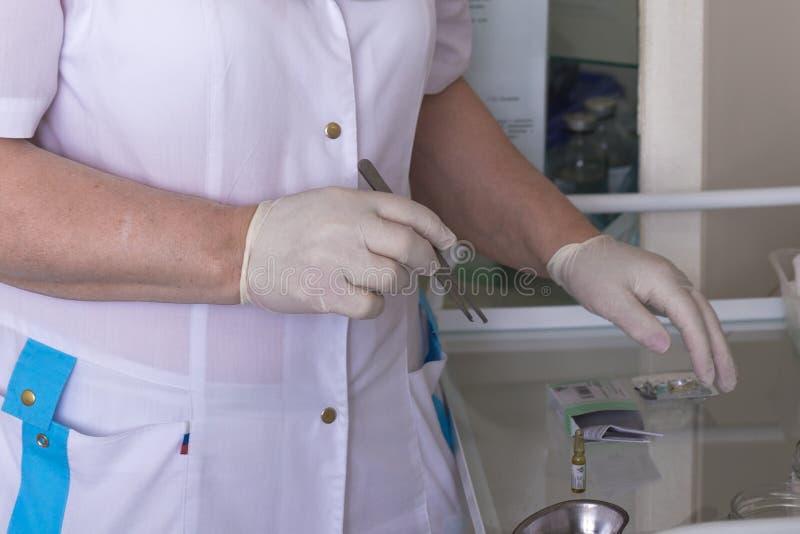 Η νοσοκόμα έβαλε λαστιχένια γάντια και πήρε τα τουίτερ. στοκ εικόνα