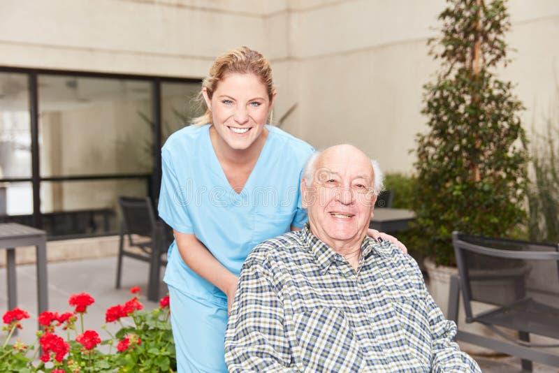 Η νοσοκόμα βάζει το ανώτερο άτομο στην αναπηρική καρέκλα στοκ φωτογραφία