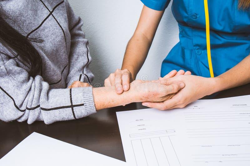 Η νοσοκόμα χρησιμοποιεί τις λαβές σφυγμού στους καρπούς των ηλικιωμένων ασθενών στοκ φωτογραφία