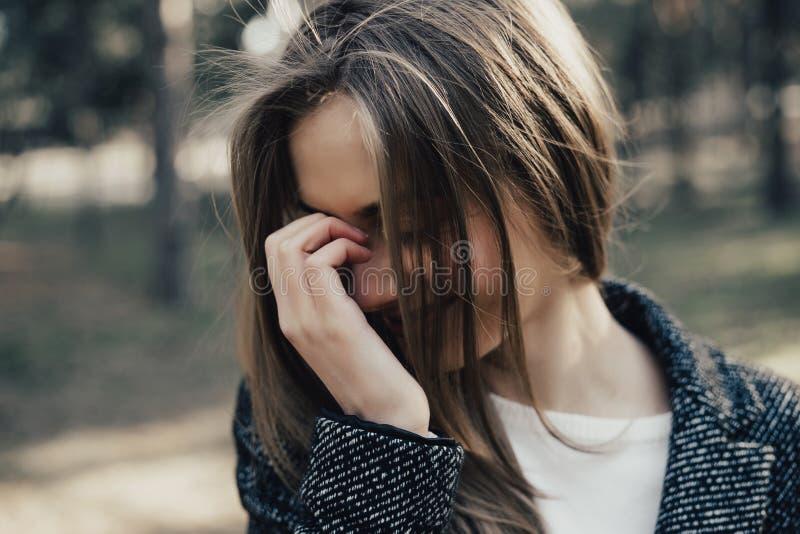 Η ντροπαλή καθιερώνουσα τη μόδα γυναίκα καλύπτει το πρόσωπό της με το χέρι της στοκ εικόνες