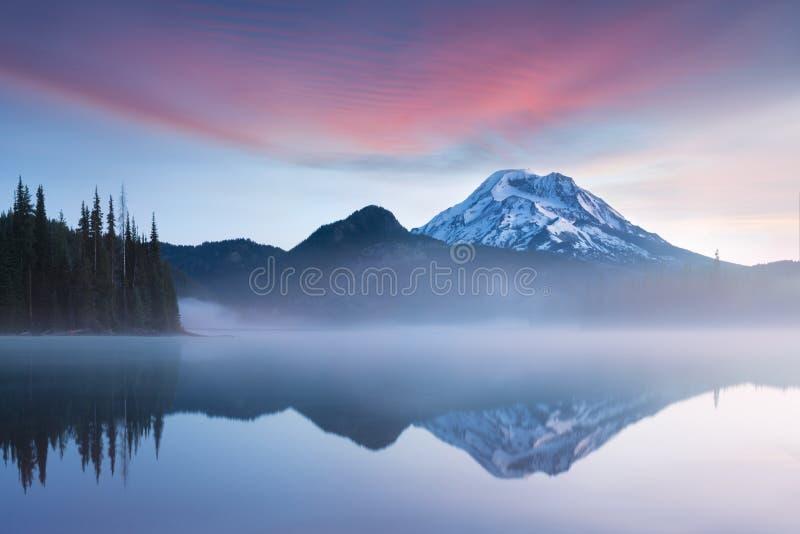 Η νότια αδελφή και η σπασμένη κορυφή απεικονίζουν πέρα από τα ήρεμα νερά της λίμνης σπινθήρων στην ανατολή στη σειρά καταρρακτών  στοκ εικόνα