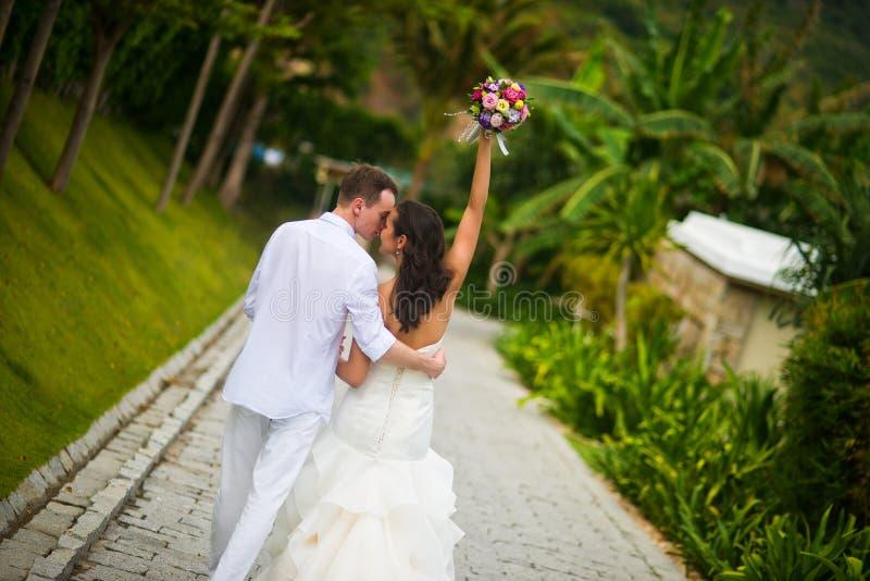 Η νύφη αύξησε το χέρι της με μια ανθοδέσμη των λουλουδιών, φιλώντας το νεόνυμφο στο πάρκο στοκ εικόνες