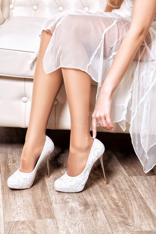 Η νύφη βάζει στα άσπρα παπούτσια στα πόδια στοκ εικόνα με δικαίωμα ελεύθερης χρήσης