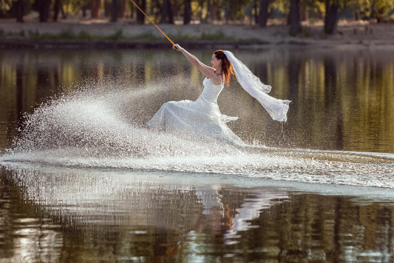 Η νύφη είναι αθλητής σε ένα φόρεμα στο σερφ στοκ εικόνες με δικαίωμα ελεύθερης χρήσης
