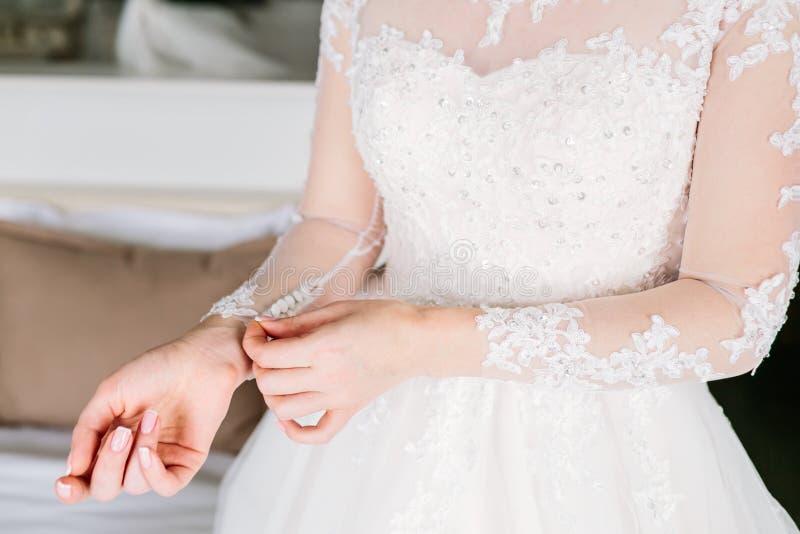 Η νύφη είναι στερεώνει τα μανίκια στο φόρεμά της, προετοιμαμένος για τη ημέρα γάμου στοκ εικόνες με δικαίωμα ελεύθερης χρήσης