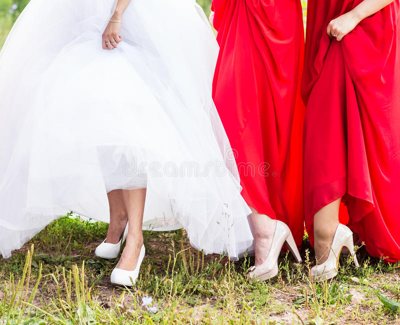 Η νύφη και οι παράνυμφοι επιδεικνύουν τα παπούτσια τους στο γάμο στοκ φωτογραφία