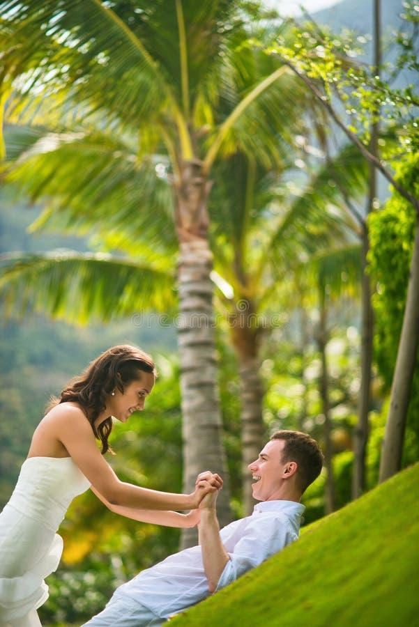 Η νύφη και ο νεόνυμφος έχουν τη διασκέδαση στην πράσινη χλόη ενάντια στους φοίνικες το καλοκαίρι στοκ εικόνα