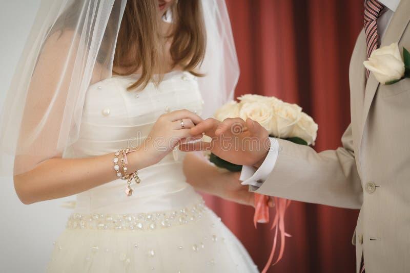 Η νύφη και ο νεόνυμφος βάζουν στα γαμήλια δαχτυλίδια στοκ φωτογραφία