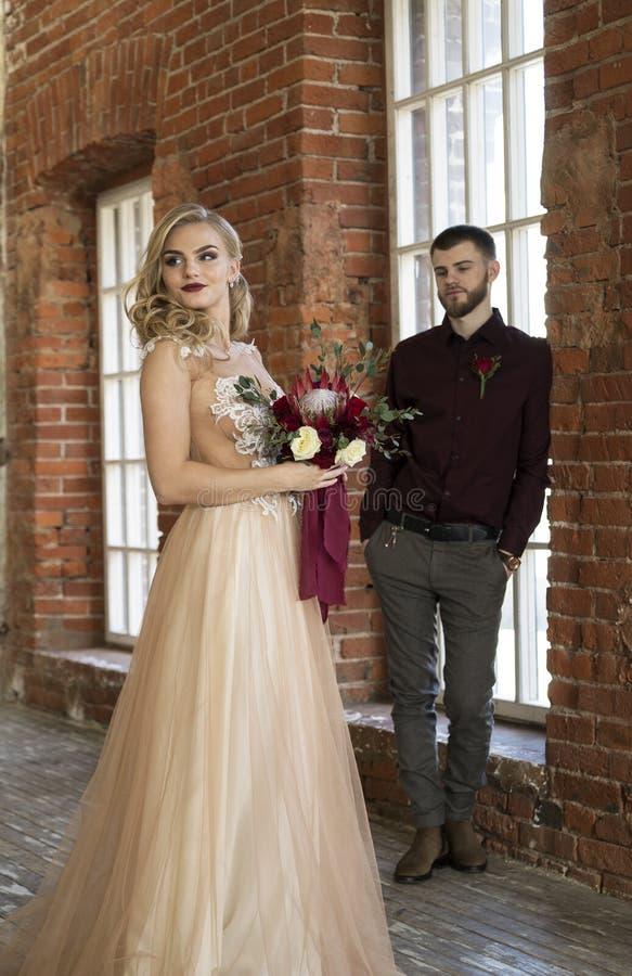Η νύφη και ο νεόνυμφος θέτουν κοντά στο παράθυρο και τον εκλεκτής ποιότητας τουβλότοιχο στοκ φωτογραφία