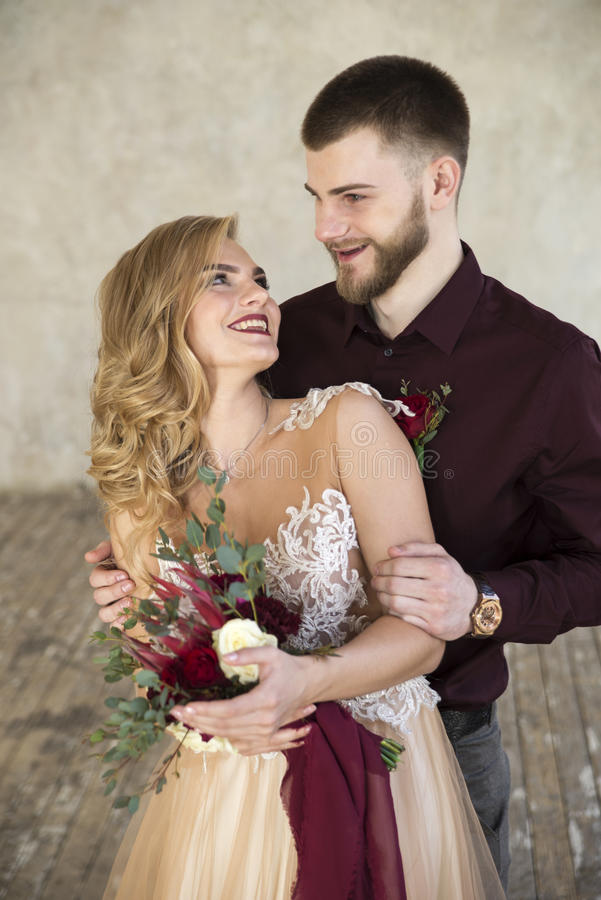Η νύφη και ο νεόνυμφος θέτουν κοντά στο παράθυρο και τον τοίχο στοκ εικόνες