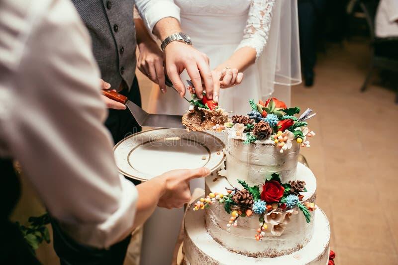 Η νύφη και ο νεόνυμφος κόβουν το αγροτικό γαμήλιο κέικ στο γαμήλιο συμπόσιο με στοκ φωτογραφία με δικαίωμα ελεύθερης χρήσης