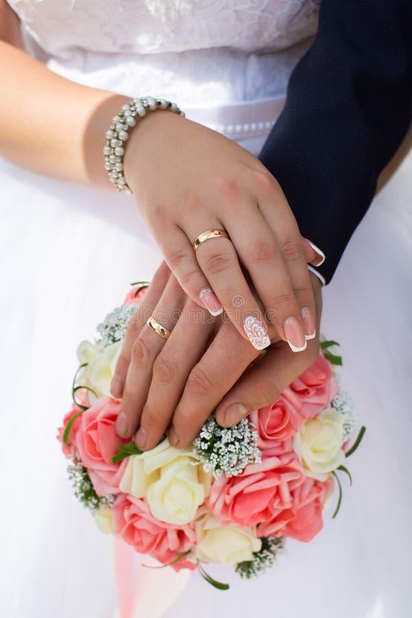 Η νύφη και ο νεόνυμφος παρουσιάζουν γαμήλια δαχτυλίδια τους στο υπόβαθρο της ανθοδέσμης στοκ εικόνα