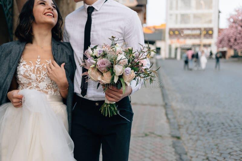 Η νύφη και ο νεόνυμφος περπατούν μέσω των οδών μιας ευρωπαϊκής πόλης Εξευγενίστε τα αγκαλιάσματα στοκ φωτογραφία