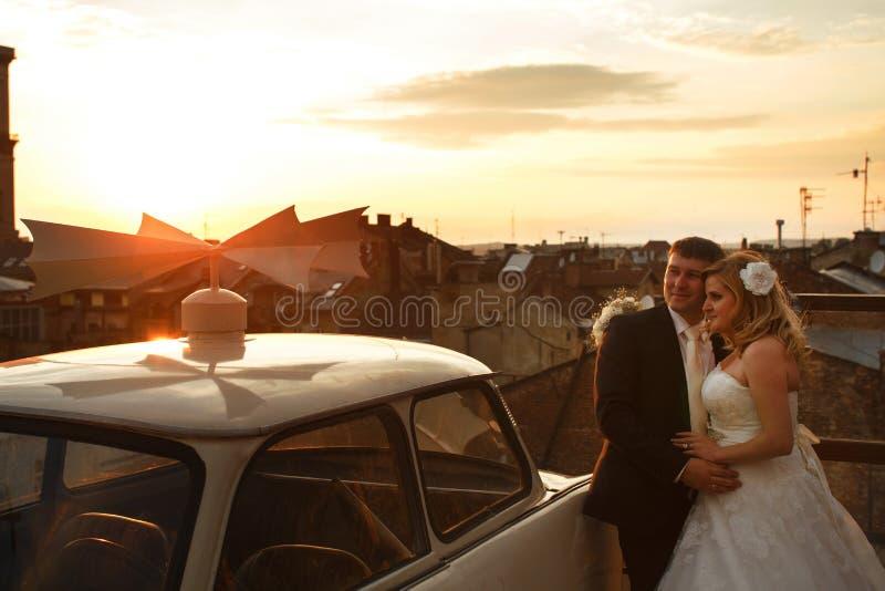 Η νύφη και ο νεόνυμφος προσέχουν το ηλιοβασίλεμα στη στέγη στοκ φωτογραφίες με δικαίωμα ελεύθερης χρήσης