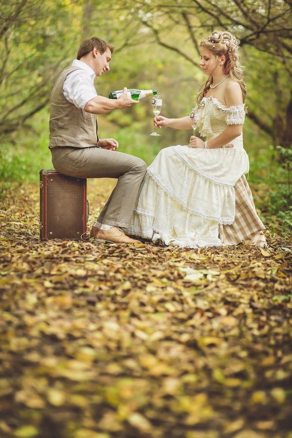 Η νύφη και ο νεόνυμφος σε μια αγροτική συνεδρίαση ύφους στο δάσος φθινοπώρου, άμπελος ποτών από τα γυαλιά στοκ εικόνες