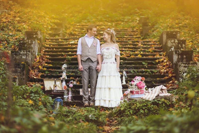 Η νύφη και ο νεόνυμφος στέκονται κοντά στα βήματα πετρών που περιβάλλονται από το γαμήλιο ντεκόρ στοκ φωτογραφία με δικαίωμα ελεύθερης χρήσης