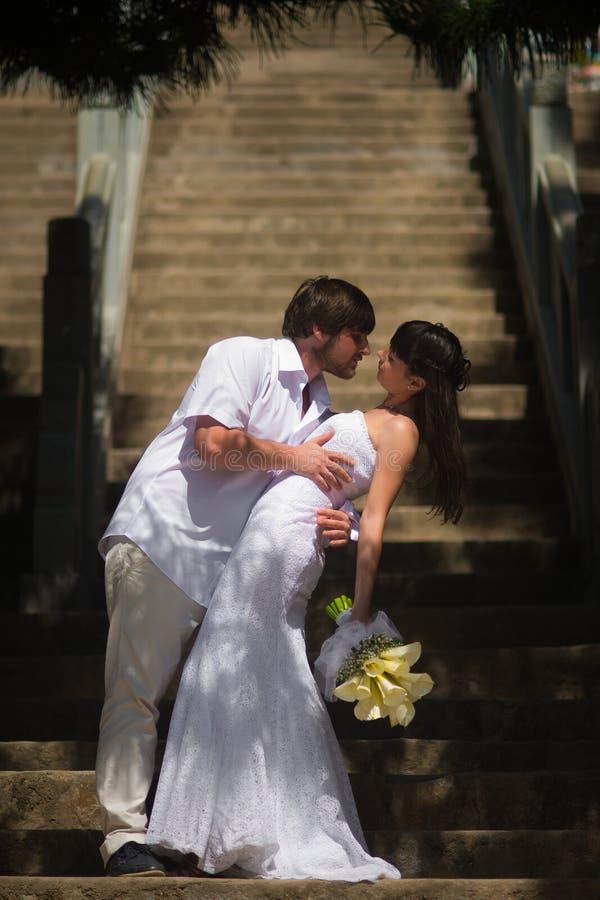 Η νύφη και ο νεόνυμφος στέκονται στα βήματα πετρών στοκ φωτογραφίες με δικαίωμα ελεύθερης χρήσης