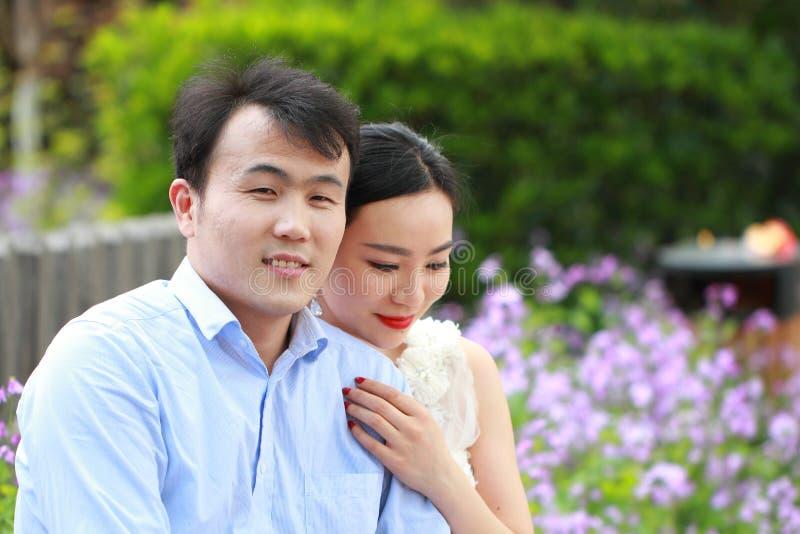 Η νύφη και ο νεόνυμφος στο γάμο ντύνουν με το κομψό hairstyle, με την άσπρη συνεδρίαση γαμήλιων φορεμάτων στον πάγκο δίπλα στο φρ στοκ εικόνα