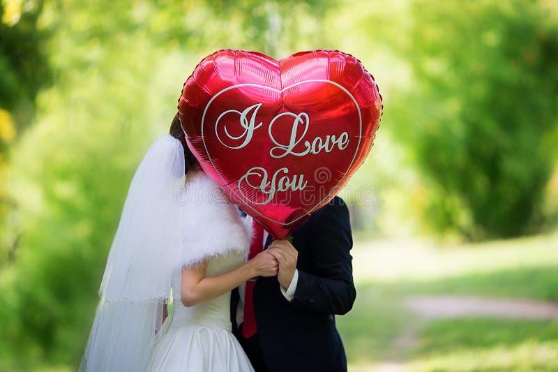 Η νύφη και ο νεόνυμφος στο πάρκο με το κόκκινο μπαλόνι με το wo στοκ εικόνες