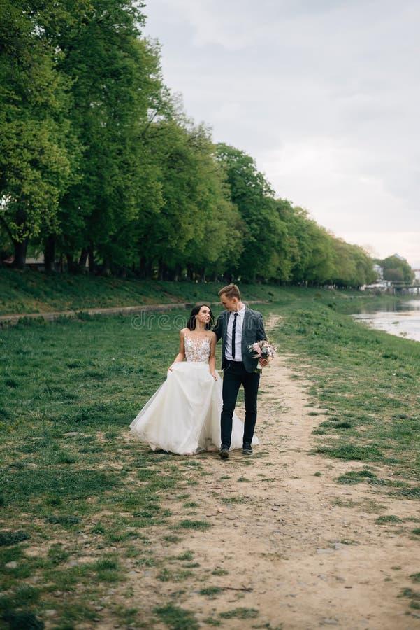 Η νύφη και ο νεόνυμφος χαρούμενοι και ευτυχείς περπατούν στο πάρκο στη ημέρα γάμου τους στοκ εικόνες