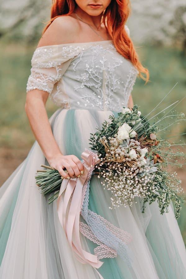 Η νύφη κρατά μια γαμήλια ανθοδέσμη άνοιξη, κινηματογράφηση σε πρώτο πλάνο στοκ εικόνα