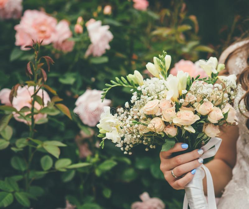 Η νύφη κρατά την όμορφη γαμήλια ανθοδέσμη στοκ εικόνα