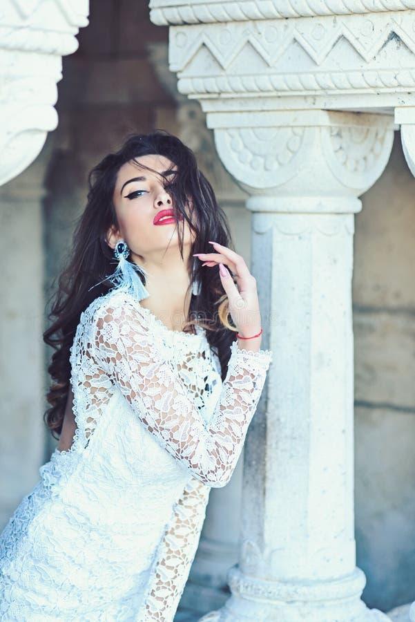 Η νύφη με το πρόσωπο makeup, κοιτάζει Η αισθησιακή γυναίκα θέτει στη στήλη Γυναίκα με το μακρύ τρίχωμα brunette Κορίτσι μόδας στο στοκ εικόνες
