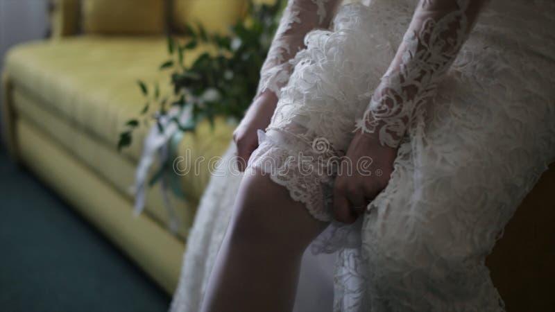 Η νύφη ντύνει τις γυναικείες κάλτσες στα πόδια Νύφη ομορφιάς σε ένα φόρεμα που φορά το γάμο γυναικείων καλτσών στο εσωτερικό Θηλυ στοκ εικόνα