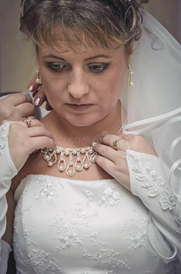 Η νύφη ντύνει το περιδέραιο γύρω από το λαιμό σας στοκ φωτογραφία