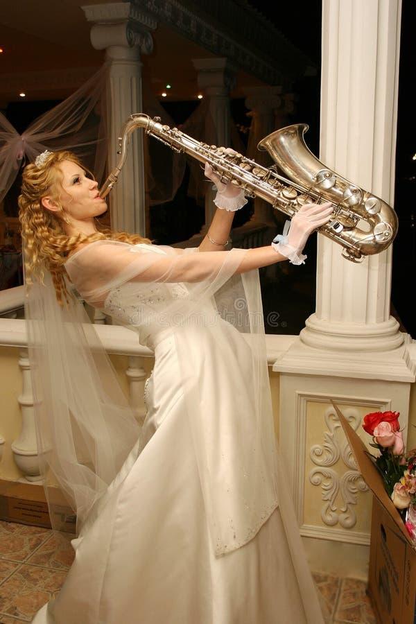 Η νύφη παίζει το saxophone στοκ εικόνες