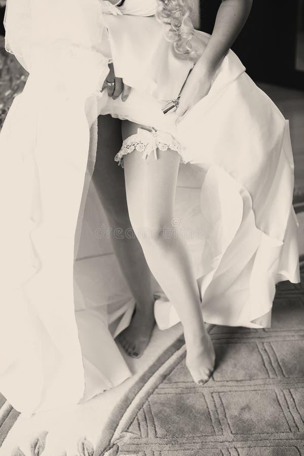 Η νύφη παρουσιάζει garter δαντελλών αυξανόμενος επάνω σε ένα γαμήλιο φόρεμα στοκ εικόνες