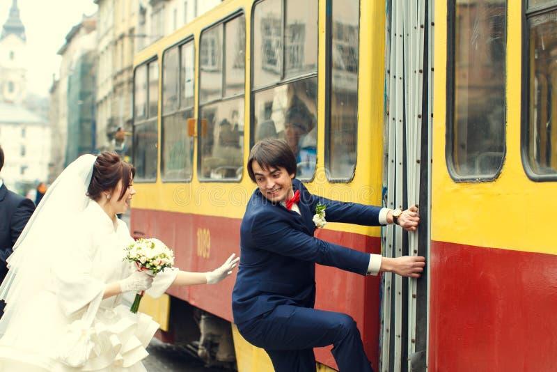 Η νύφη προσπαθεί να πιάσει έναν νεόνυμφο που αναρριχείται σε ένα τραμ στοκ φωτογραφία