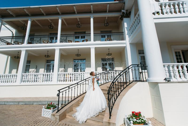 Η νύφη σε ένα λευκό σαν το χιόνι φόρεμα αναρριχείται στα σκαλοπάτια του ελεφαντόδοντου Το κορίτσι κρατά το μακρύ τραίνο της με το στοκ φωτογραφία με δικαίωμα ελεύθερης χρήσης