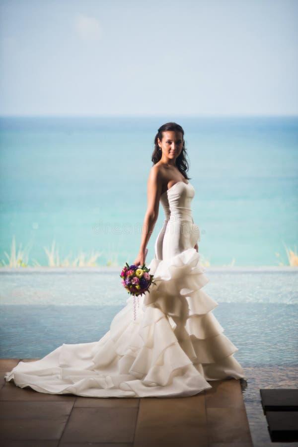 Η νύφη σε ένα πολυτελές άσπρο φόρεμα στέκεται στο υπόβαθρο της θάλασσας στοκ εικόνες