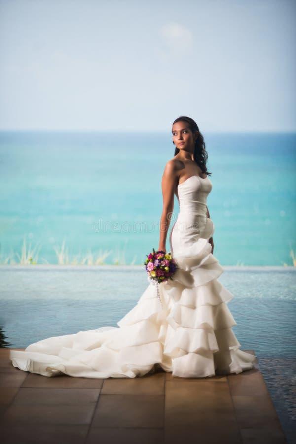 Η νύφη σε ένα πολυτελές άσπρο φόρεμα στέκεται στο υπόβαθρο του ωκεανού και κοιτάζει μακριά στοκ εικόνα