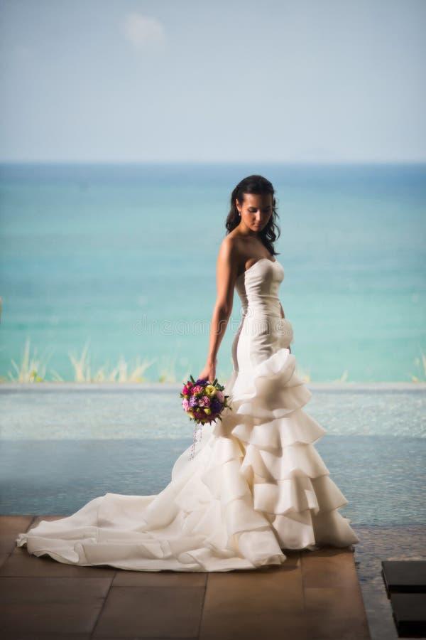 Η νύφη σε ένα πολυτελές άσπρο φόρεμα στέκεται στο υπόβαθρο του ωκεανού στοκ εικόνες με δικαίωμα ελεύθερης χρήσης