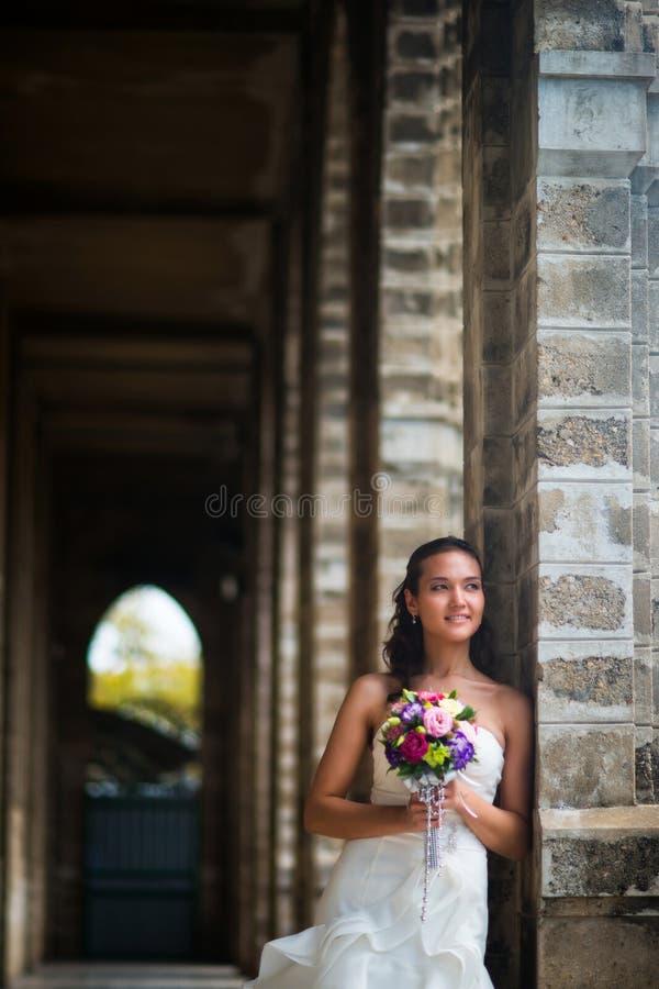Η νύφη σε ένα όμορφο άσπρο φόρεμα στέκεται σε μια στοά των τοίχων πετρών σε ένα όμορφο άσπρο γαμήλιο φόρεμα με μια ανθοδέσμη του  στοκ φωτογραφίες με δικαίωμα ελεύθερης χρήσης