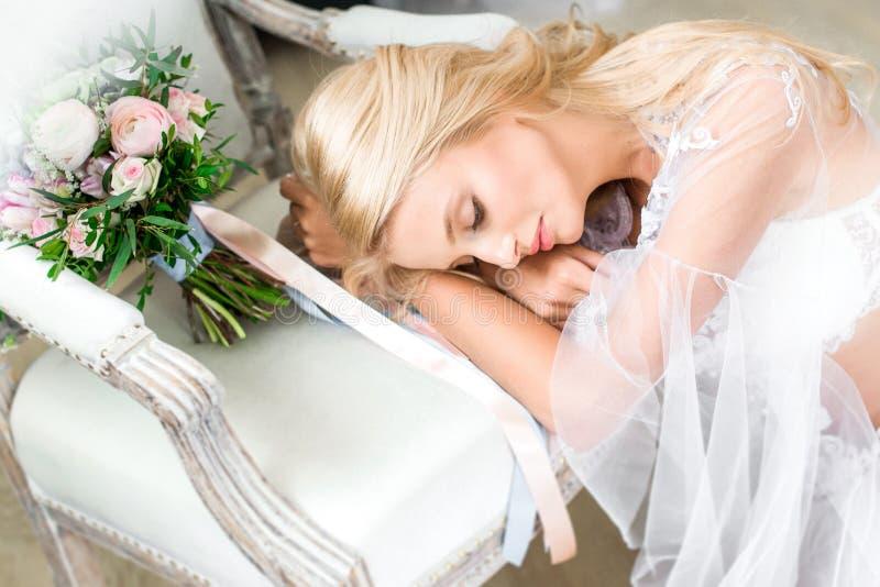 Η νύφη στηρίζεται το κεφάλι της σε ετοιμότητα της σε μια καρέκλα στοκ εικόνες με δικαίωμα ελεύθερης χρήσης