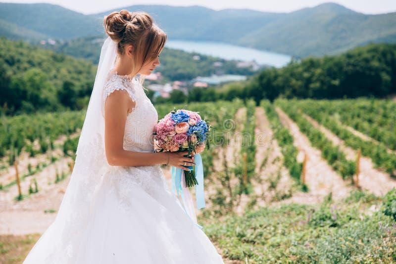 Η νύφη στο σχεδιάγραμμα σε ένα υπόβαθρο της όμορφων πρασινάδας και του ουρανού θαυμάζει τη γαμήλια ανθοδέσμη της στοκ φωτογραφία με δικαίωμα ελεύθερης χρήσης