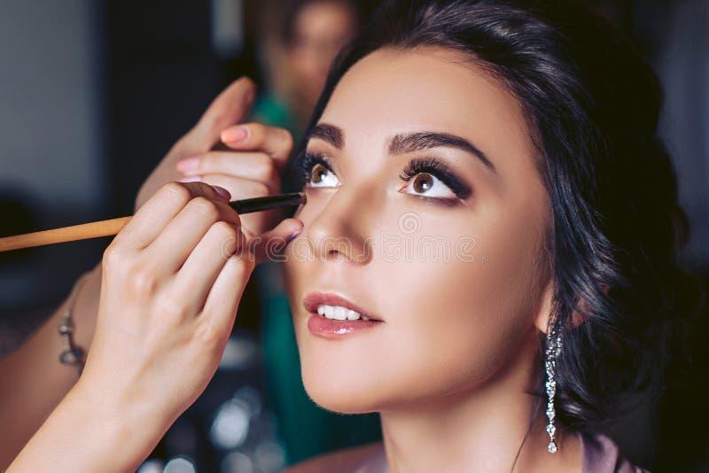 Η νύφη τίθεται στο makeup πριν από τη γαμήλια τελετή στοκ εικόνες