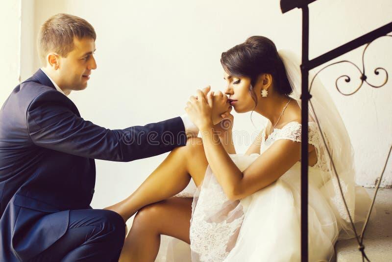 Η νύφη φιλά το δαχτυλίδι του νεόνυμφου στοκ εικόνα