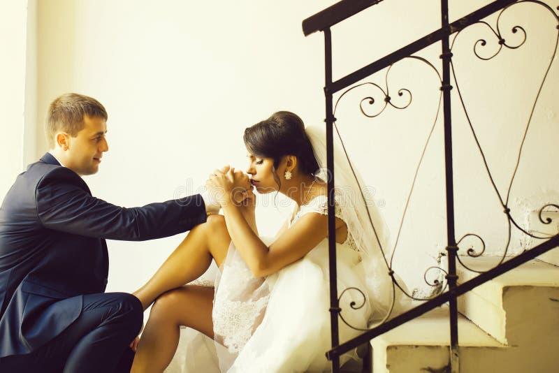 Η νύφη φιλά το δαχτυλίδι του νεόνυμφου στοκ φωτογραφία