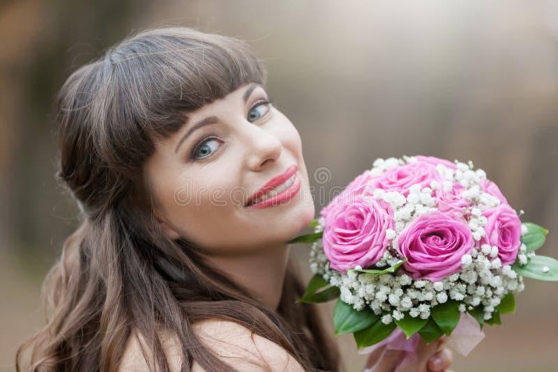 Η νύφη Brunette, ανθοδέσμη τριαντάφυλλων, χαμόγελο, κλείνει επάνω στοκ εικόνες