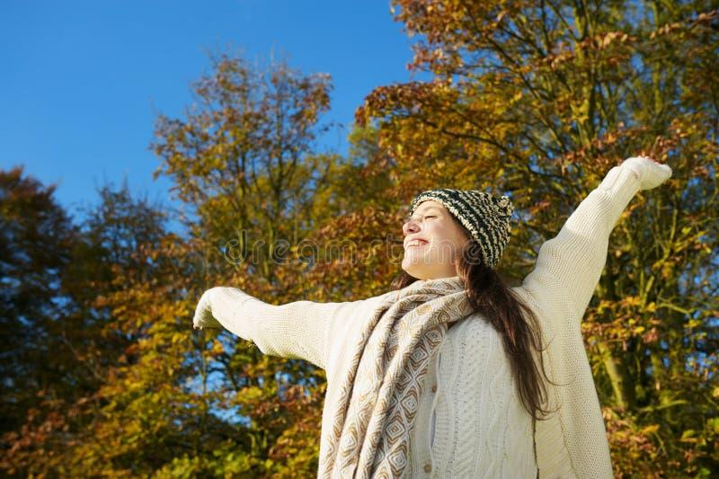 Η ξένοιαστη γυναίκα που απολαμβάνει τον ήλιο φθινοπώρου με τα όπλα στοκ εικόνα